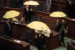 "Pro-democracy lawmakers walk out in protest before the policy address of Hong Kong Chief Executive Leung Chun-ying in the legislative council in Hong Kong on January 14, 2015. Leung took a hard line on political reform in his annual policy address on January 14, saying the city does not have ""absolute autonomy"" from China and urged support for the controversial blueprint for leadership elections. AFP PHOTO / Philippe Lopez"