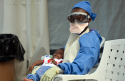 A Liberian health worker holds a baby infected with the Ebola virus on October 18, 2014 at the NGO Medecins Sans Frontieres (Doctors Without Borders) Ebola treatment center in Monrovia. The death toll in the world's worst-ever Ebola outbreak has shot past 4,500, killing at least half of the more than 9,000 people infected, fresh World Health Organization figures showed on October 17. AFP PHOTO / ZOOM DOSSO