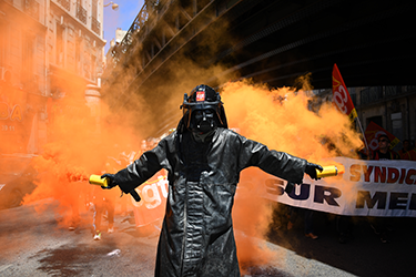 A man wearing a Dark Vador mask holds smoke flares during a demonstration against the French government's planned labour law reforms, on June 2, 2016 in Marseille, southern France.  France suffered a third day of rail strikes on June 2, 2016, but fears of