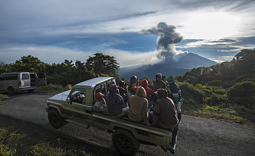 Farmers are transported on the back of a truck as the Turrialba volcano erupts in the background on May 20, 2016, in Cartago, Costa Rica. AFP PHOTO / Ezequiel Becerra