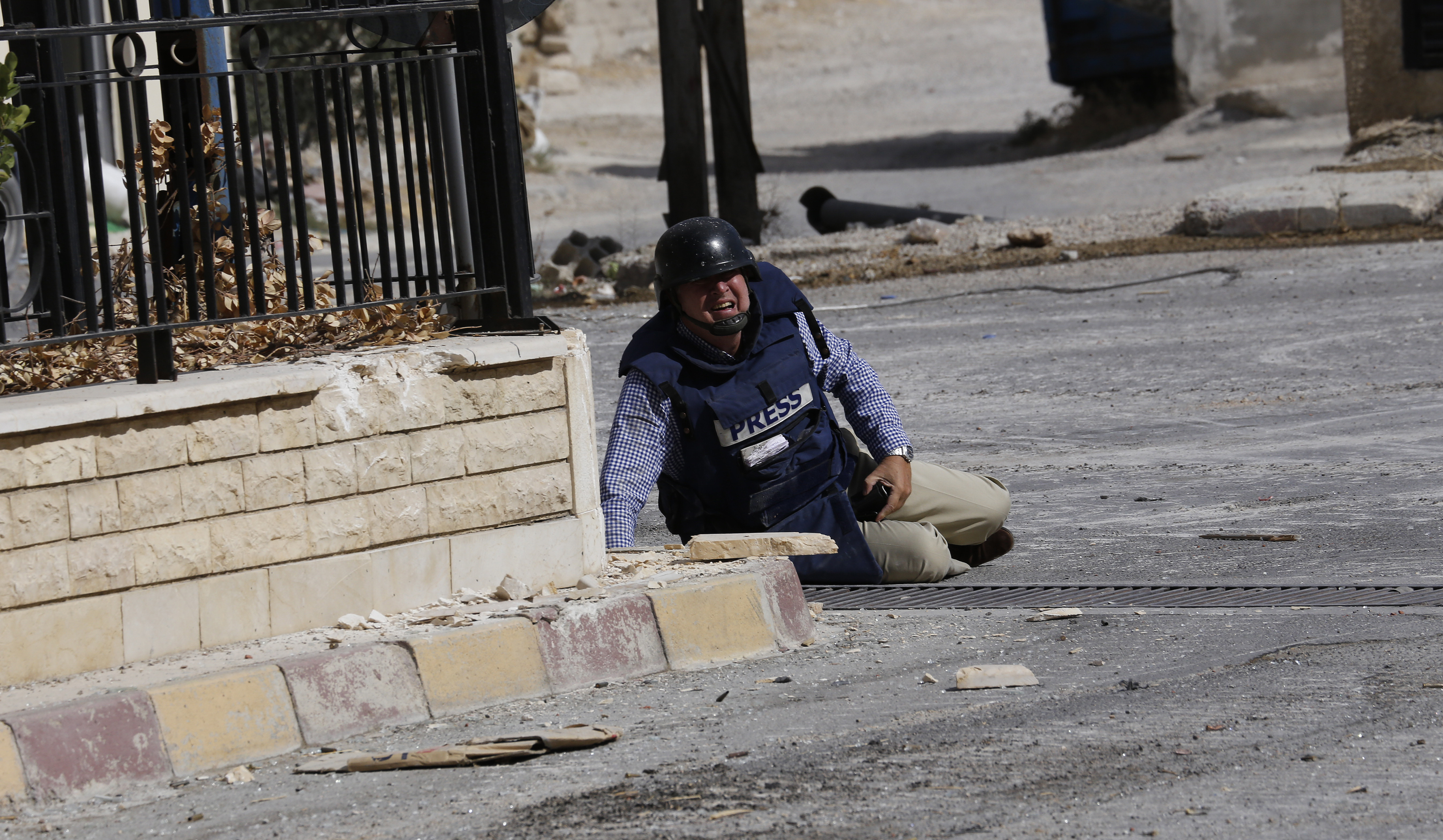 AFP reporter Sammy Ketz lies on the ground during sniper fire in the ancient Christian Syrian town of Maalula, on September 18, 2013